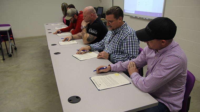 Spring 2019 manufacturing apprenticeship participants preparing to sign their agreement.